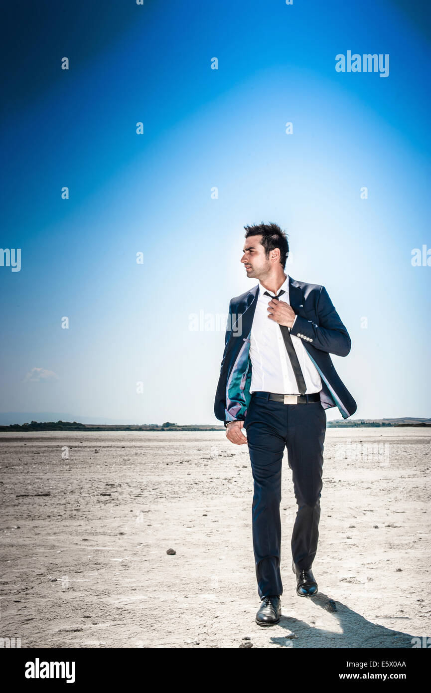 Young businessman striding through desert landscape alone - Stock Image
