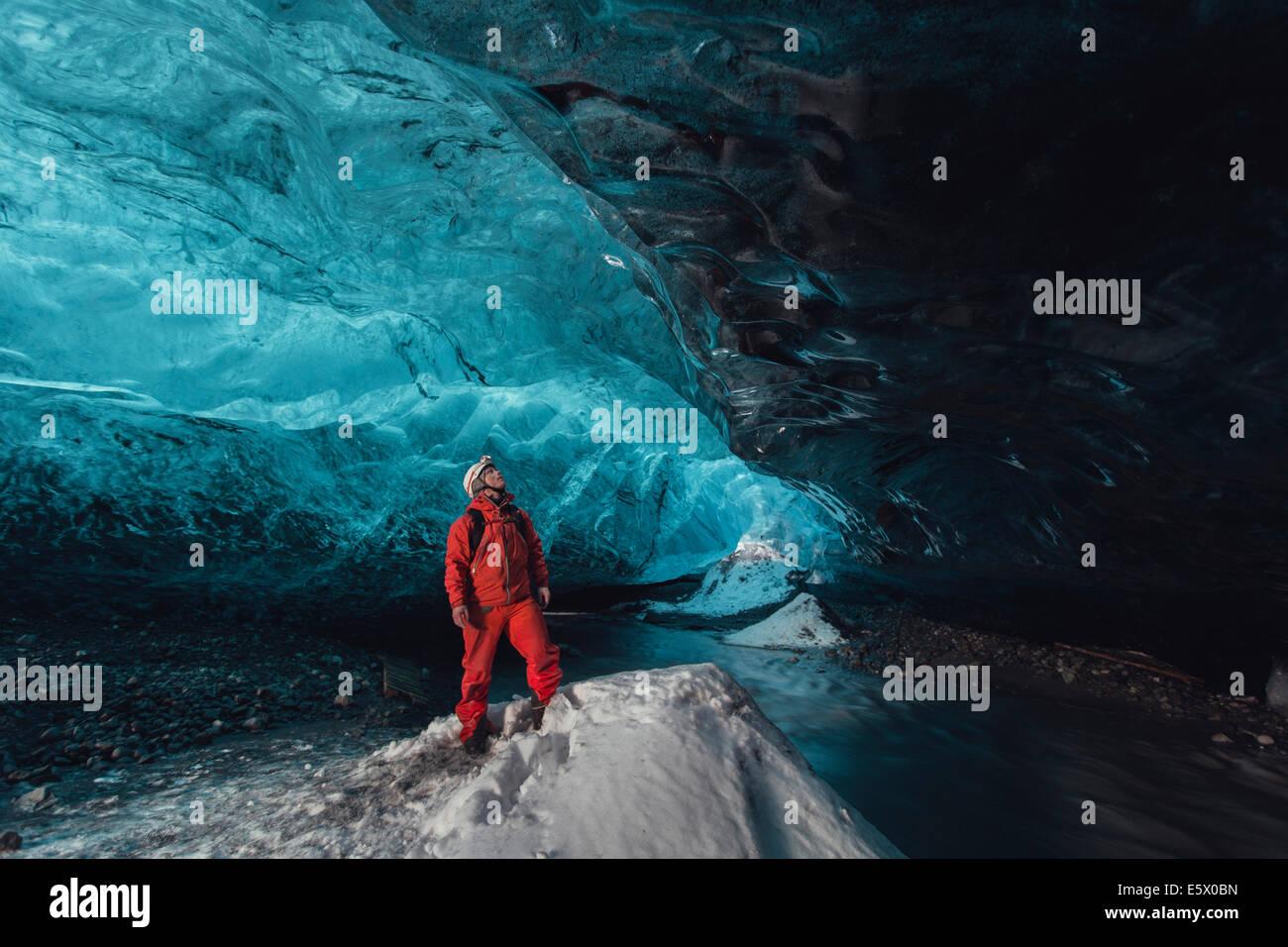 Man gazing upward in ice cave, Vatnajokull Glacier, Vatnajokull National Park, Iceland - Stock Image