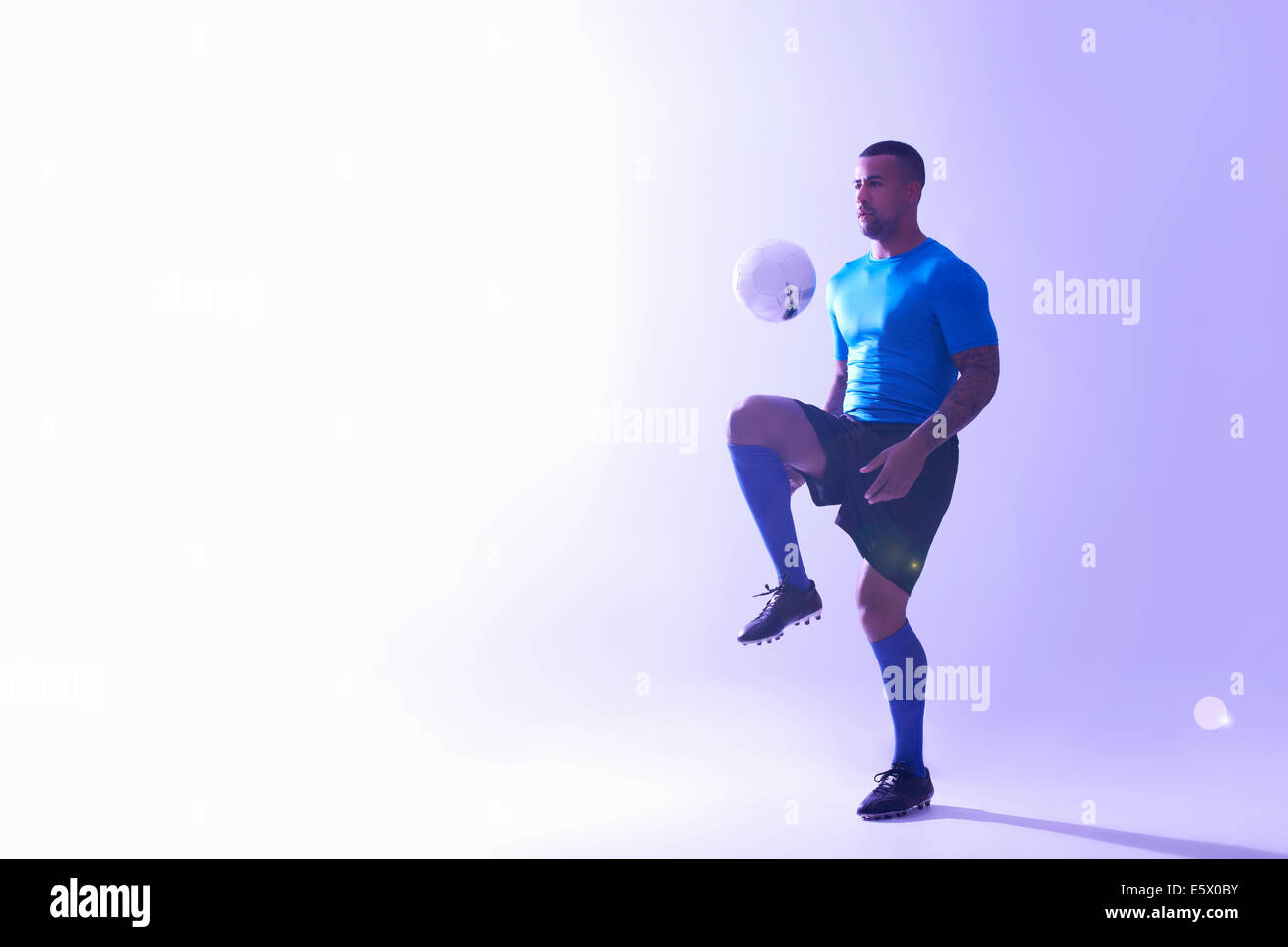 Studio shot of young male soccer player keeping ball mid air with knee - Stock Image