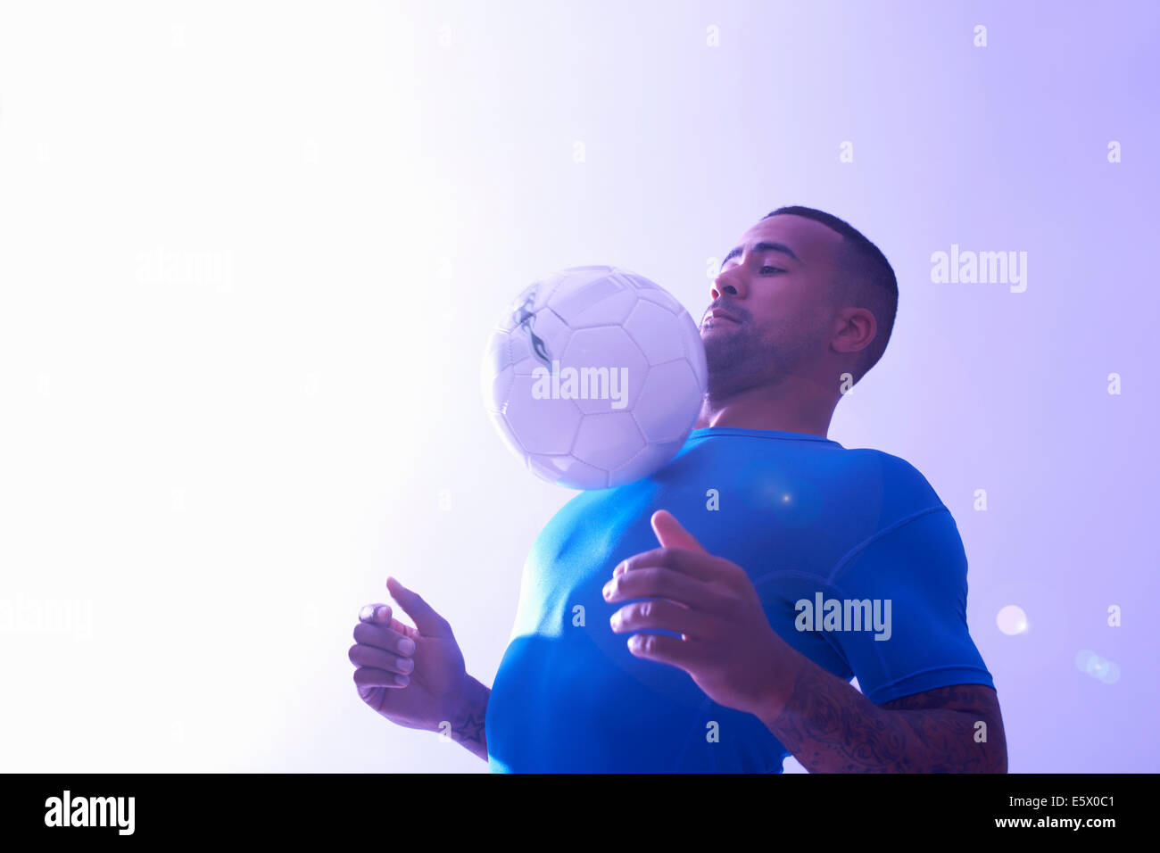 Studio shot of young male soccer player keeping ball mid air with chest - Stock Image