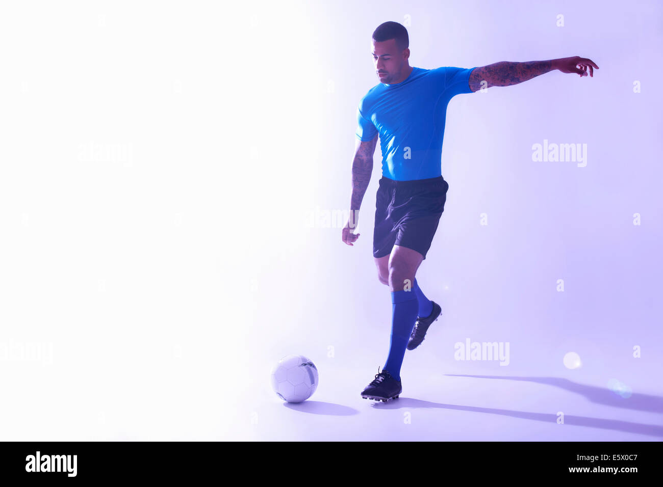 Studio shot of young male soccer player kicking the ball - Stock Image