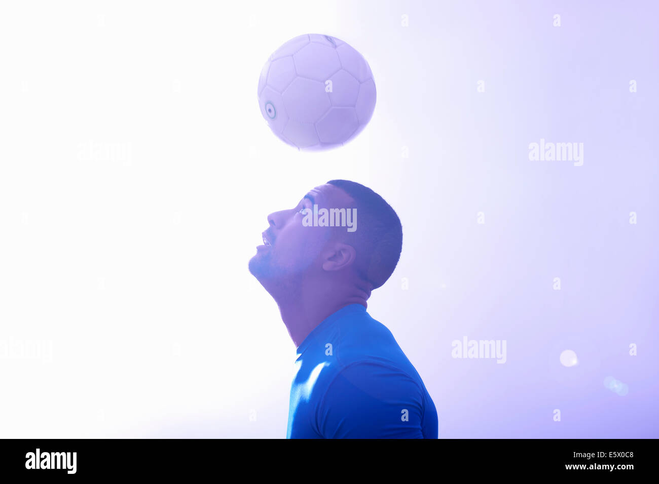 Studio shot of young male soccer player keeping ball mid air with header - Stock Image