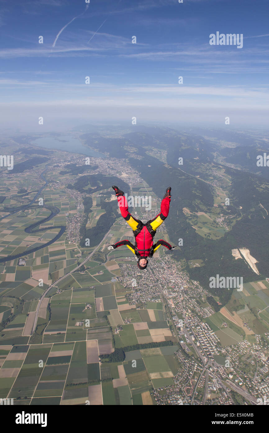 Female skydiver free falling upside down over Grenchen, Berne, Switzerland - Stock Image