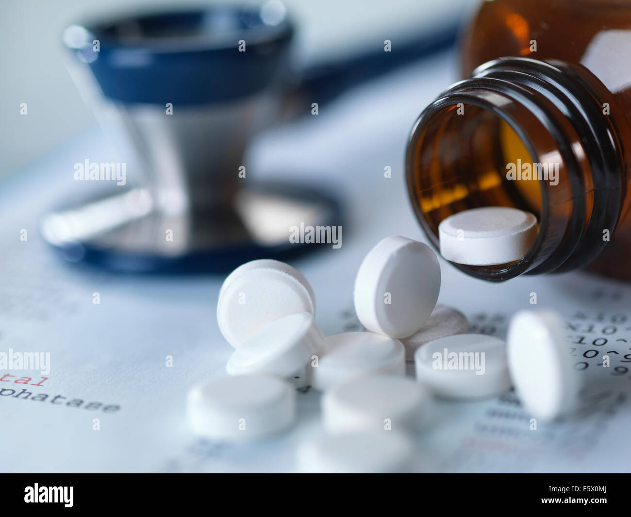 Close up of stethoscope and pain killers pouring onto medical test results - Stock Image