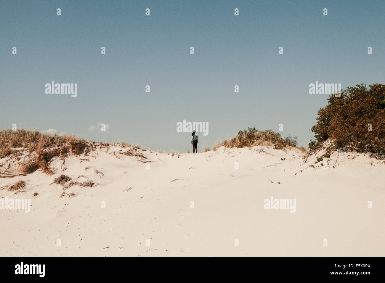Mid adult woman standing on sand dunes, Jones beach, New York State, USA - Stock Image