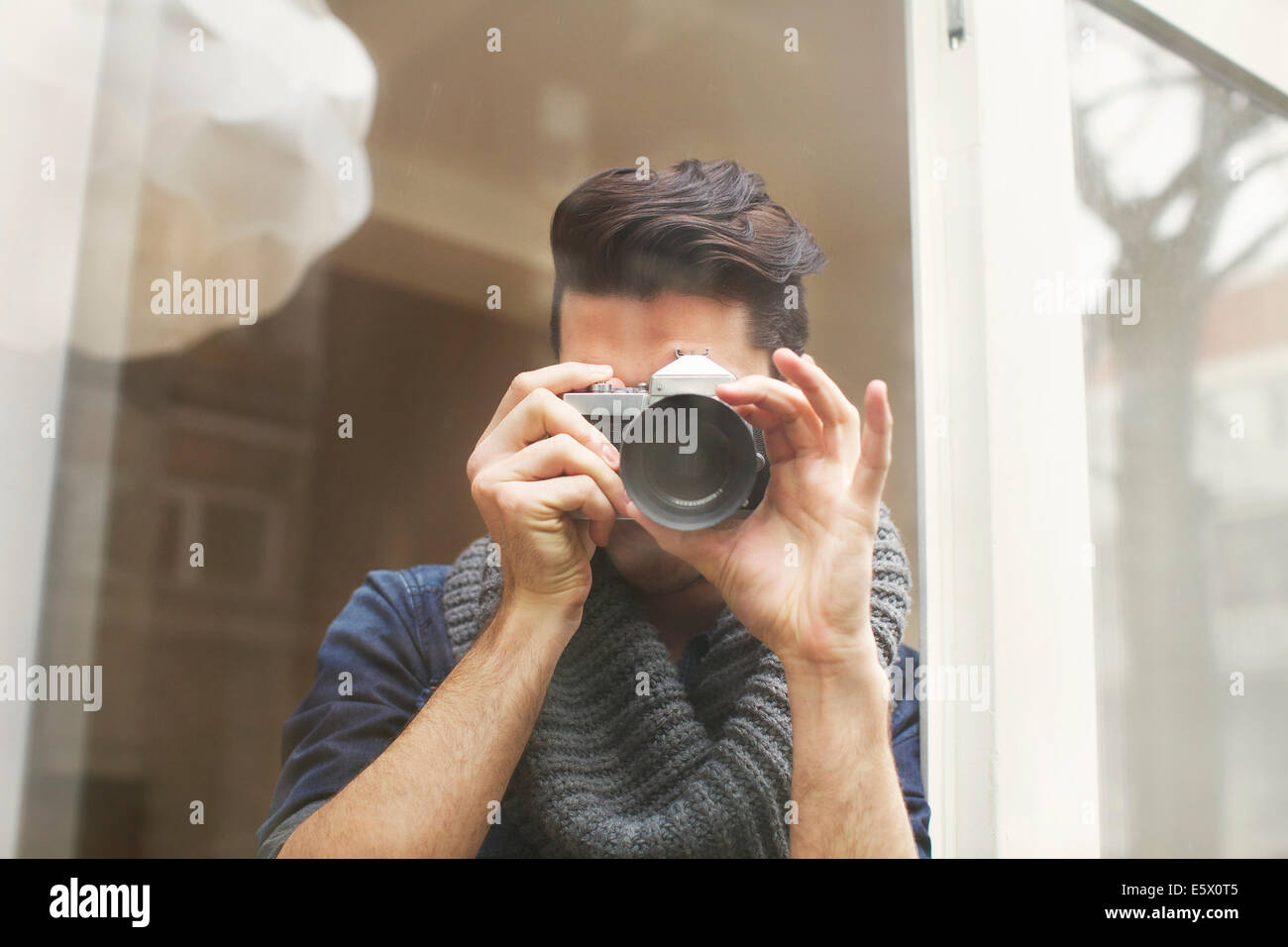 Portrait of young man photographing with SLR camera - Stock Image