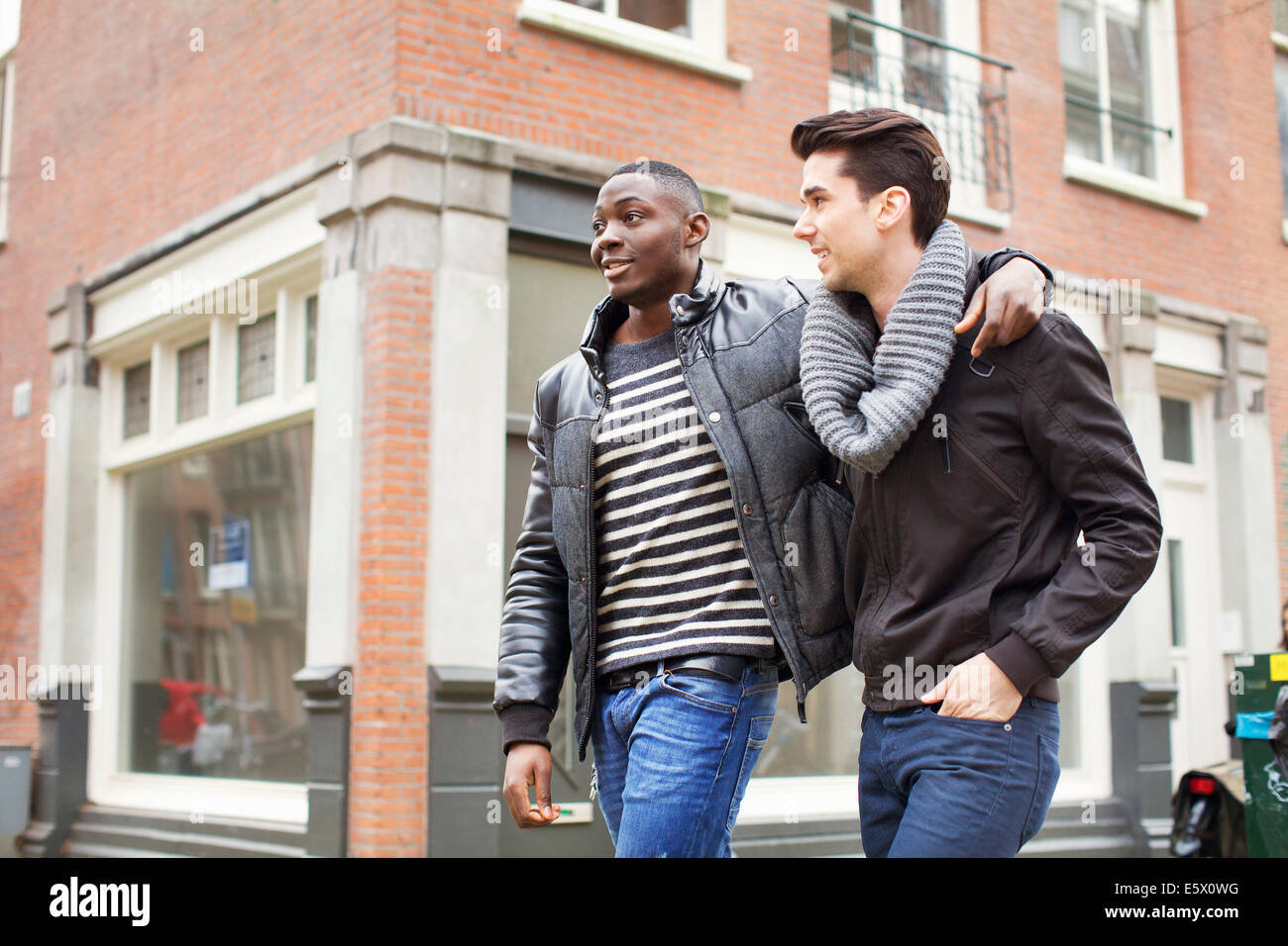 Two young men strolling down the street with arms around each other - Stock Image