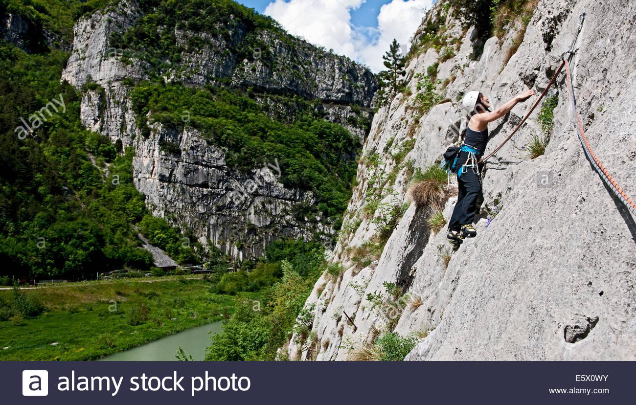 Woman climber traversing on multi pitch route, Amazziona at Piccolo Dain Parete della Centrale, Sarche, Trentino, - Stock Image