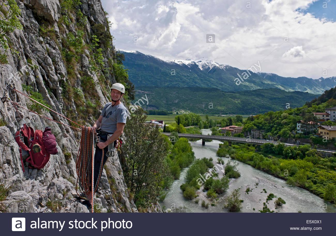 Male climber at belay point on multi pitch route, Amazziona at Piccolo Dain Parete della Centrale, Sarche, Trentino, - Stock Image