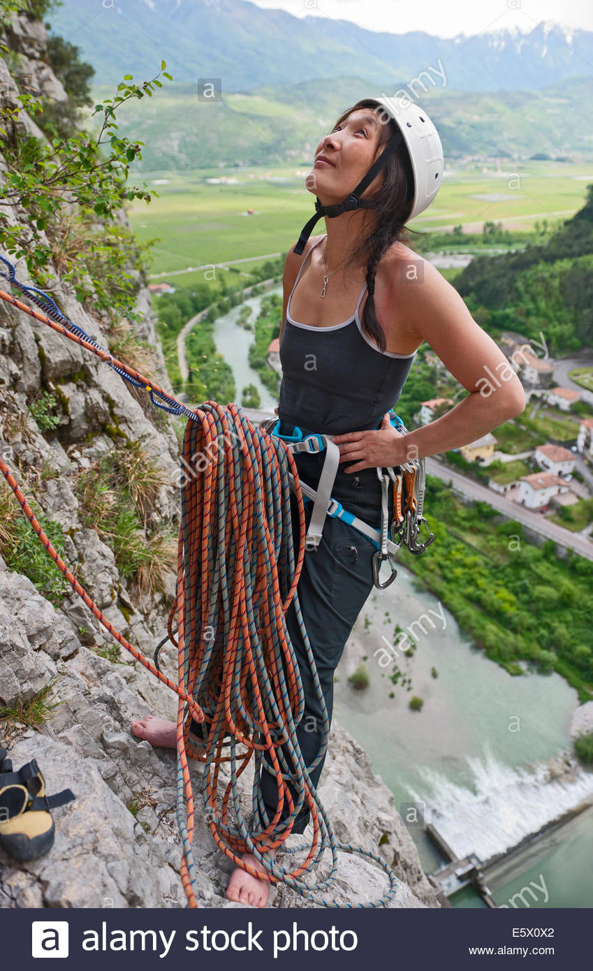 Female climber at belay point on multi pitch route, Amazziona at Piccolo Dain Parete della Centrale, Sarche, Trentino, - Stock Image