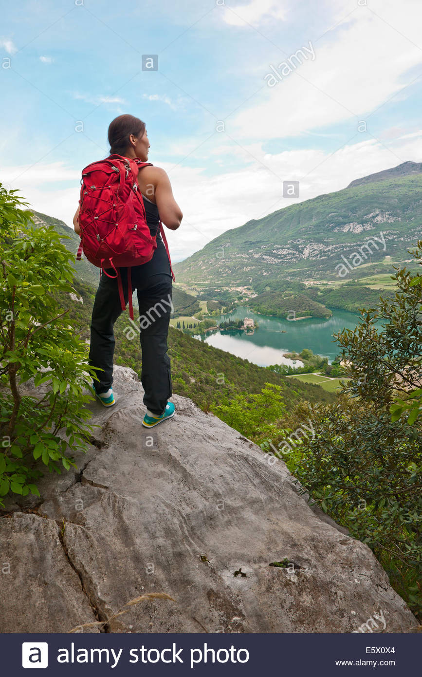 Female climber looking down over lake Tablino and castle, Sarche, Trentino, Italy - Stock Image