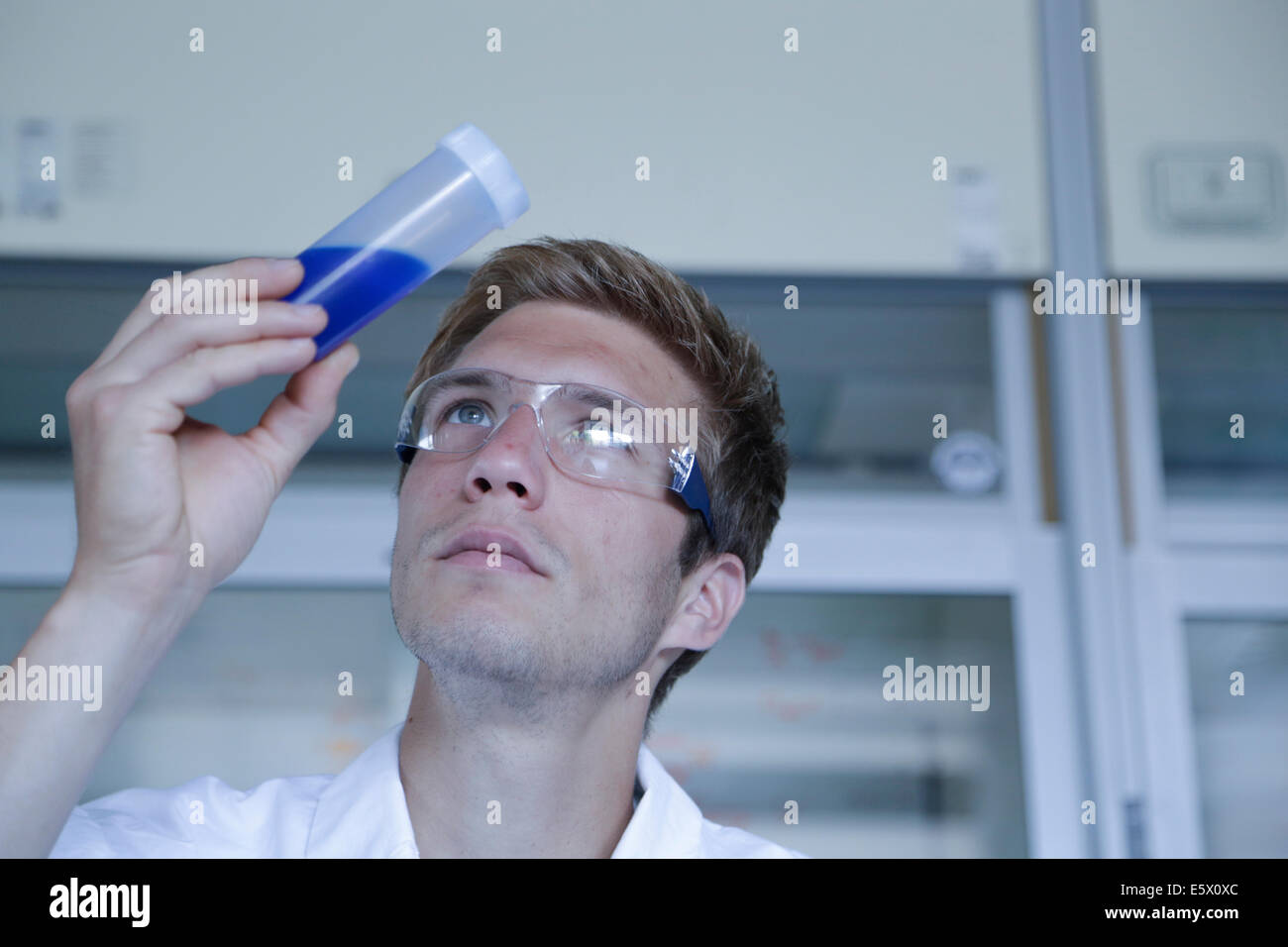 Male scientist looking up at sample in plastic bottle in lab - Stock Image