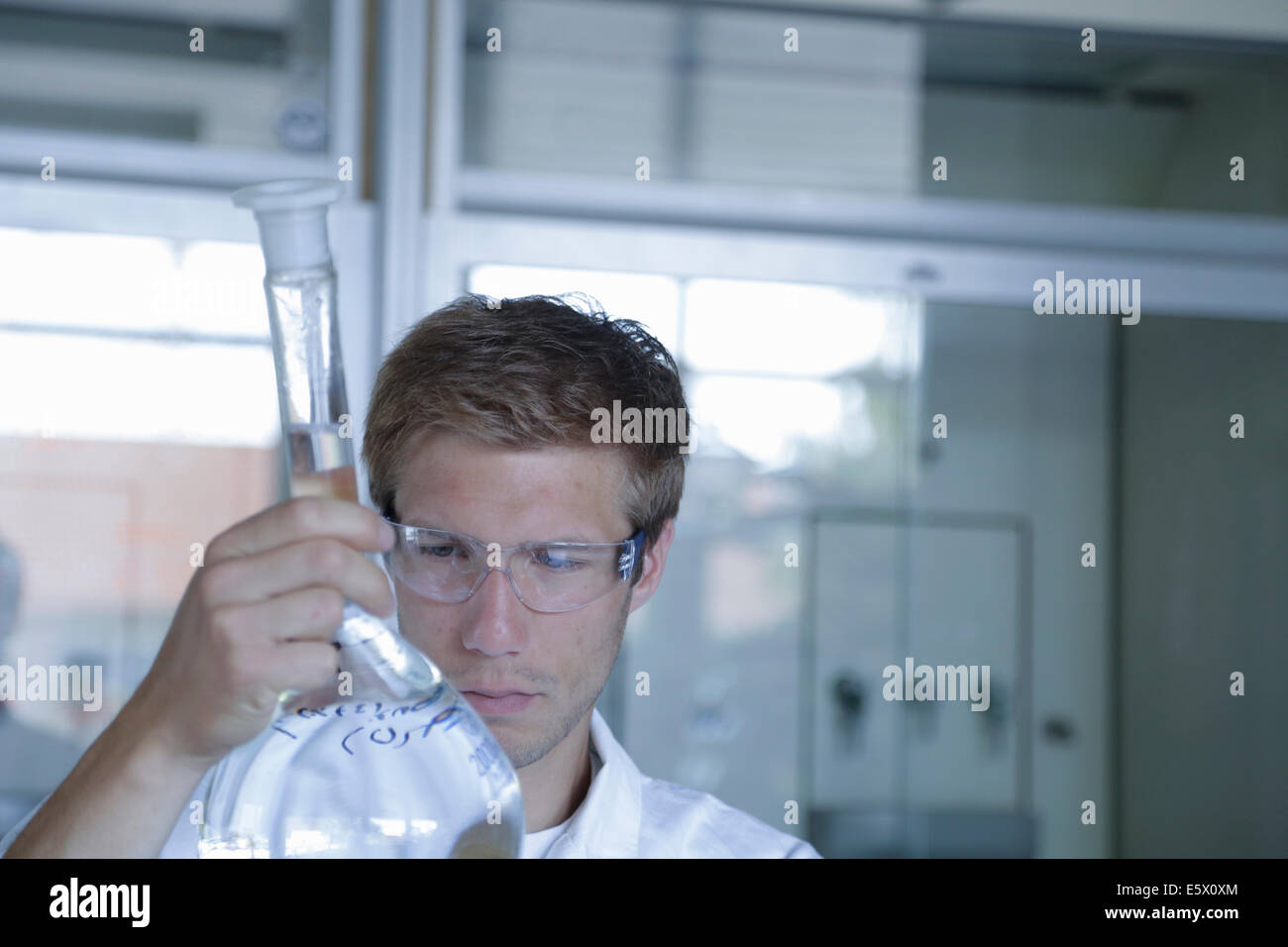 Young male scientist analyzing volumetric flask in lab - Stock Image