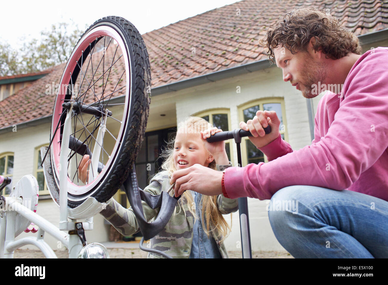 Father and daughter mending bike Stock Photo