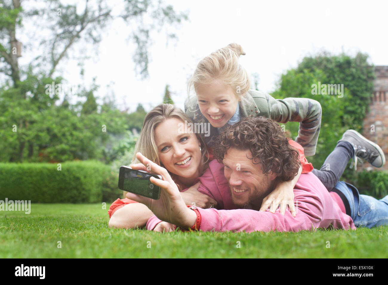 Father photographing family lying on lawn Stock Photo
