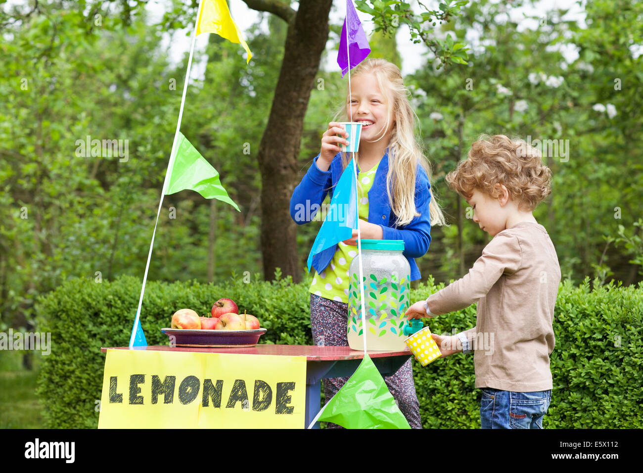 Siblings at their lemonade stand in their garden Stock Photo