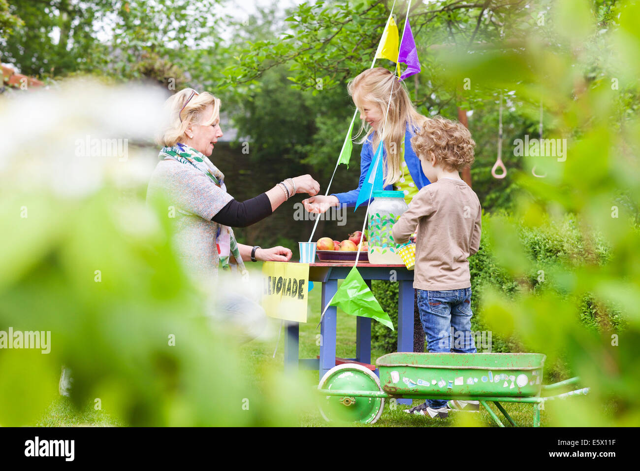 Grandmother buying lemonade from grandchildren's stand Stock Photo
