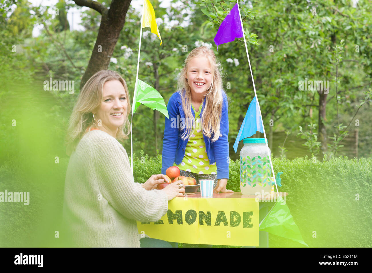 Mother buying lemonade from daughter's stand - Stock Image