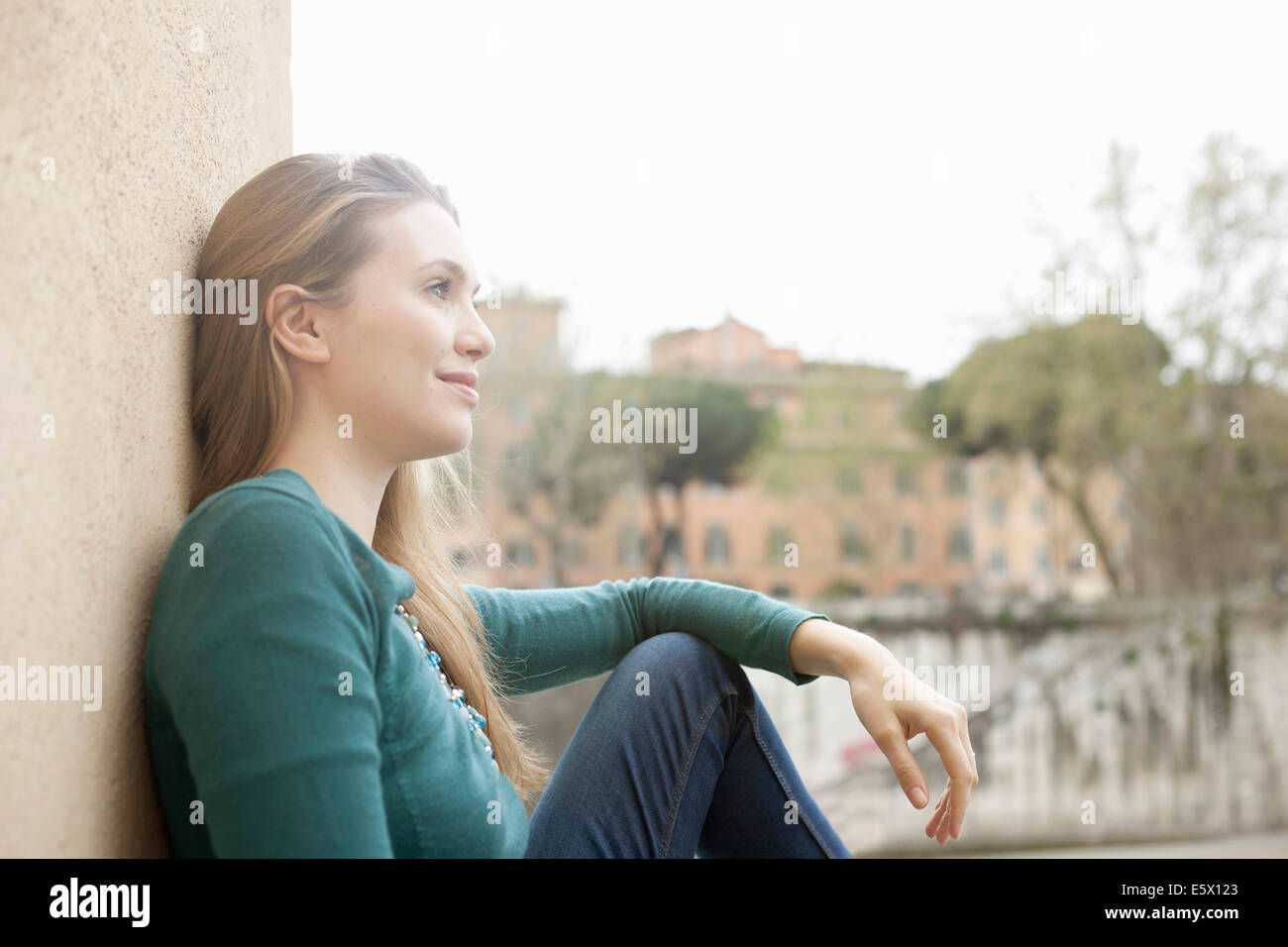 Young woman leaning against wall, Isola Tiberina, Rome, Italy - Stock Image