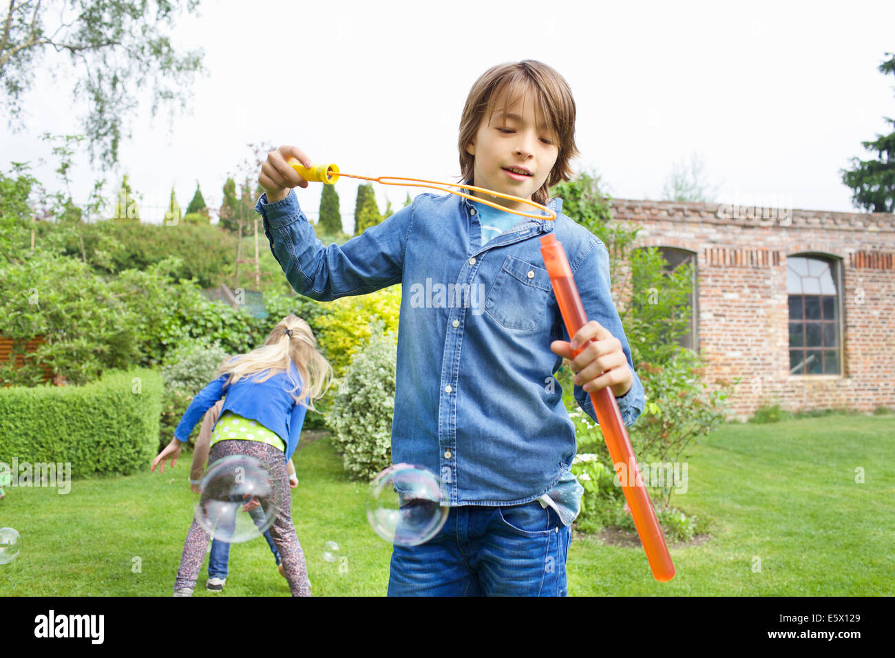 SIblings playing with soap bubbles in garden - Stock Image
