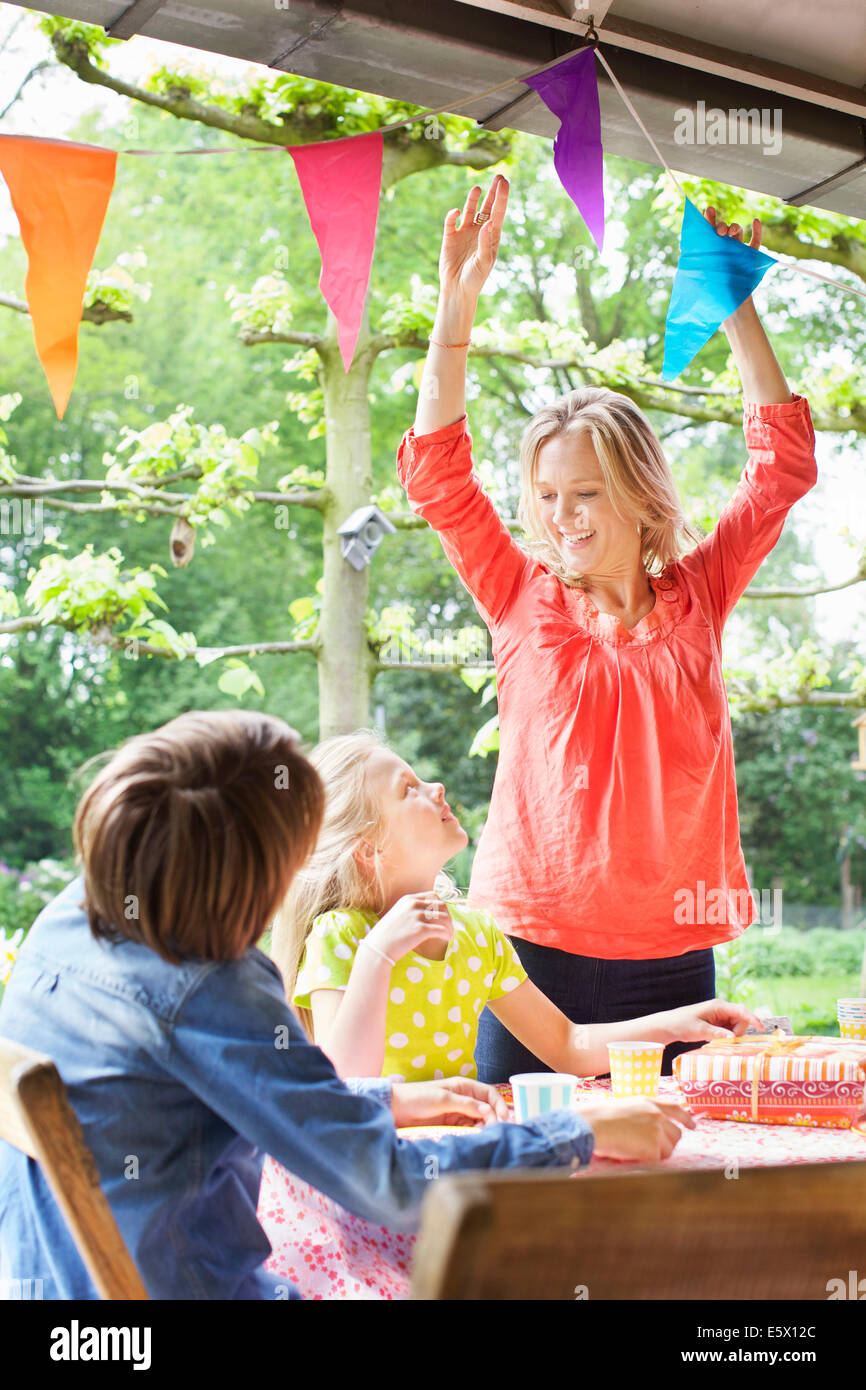 Mother chatting with children and putting up bunting - Stock Image