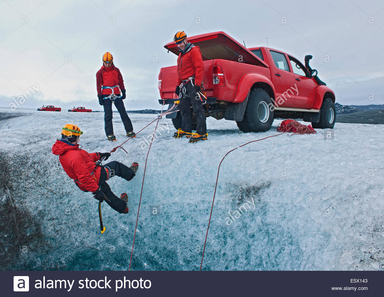 Ice climbers on glacier using the 4X4 as a belay anchor to lower off into the icecave, Breidamerkurjokull, East - Stock Image