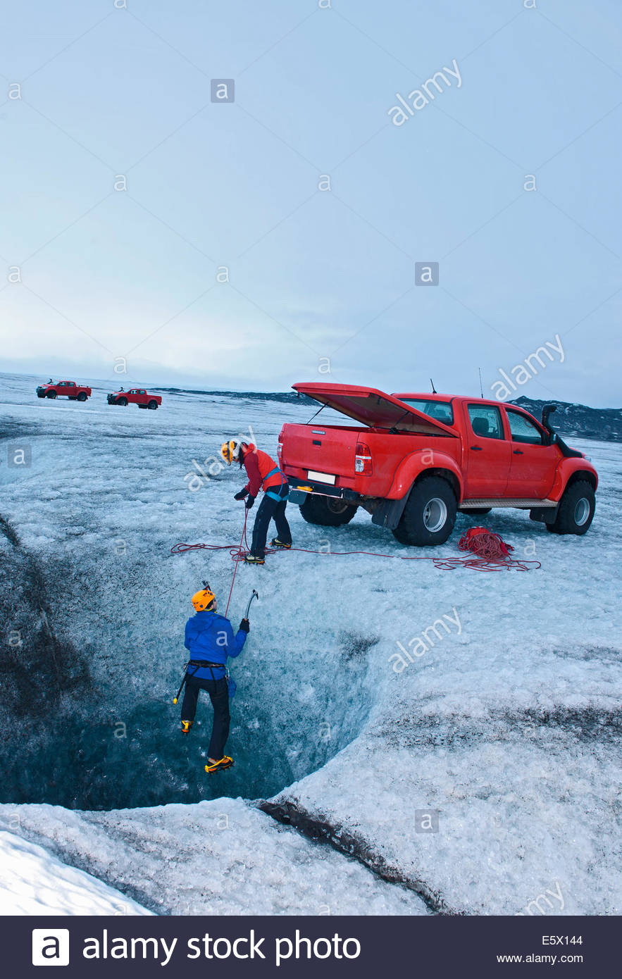 Ice climbers on glacier using 4X4 as a belay anchor, for climbing out of an icecave, Breidamerkurjokull, East Iceland, - Stock Image