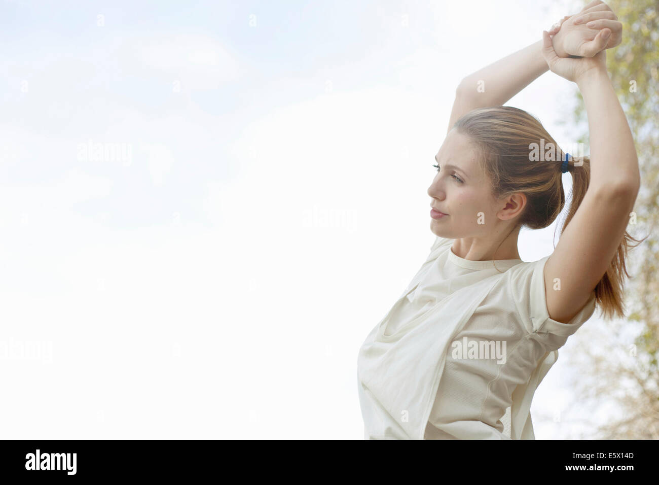Young woman stretching arms before exercise - Stock Image