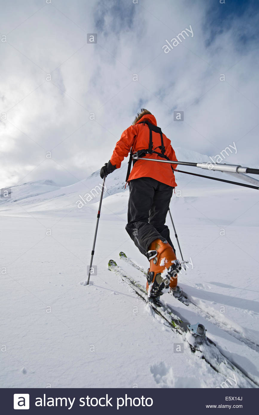 Female touring skier pulling an expedition sled in snow, Oxnadalsheidi, North Iceland, Iceland - Stock Image