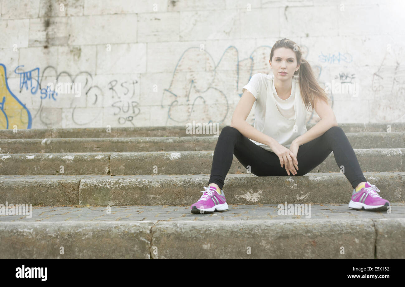 Sporty young woman sitting on steps Stock Photo