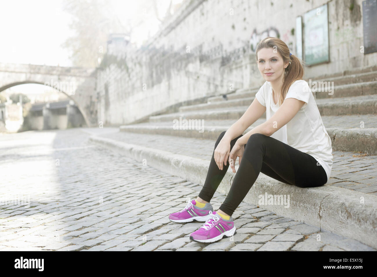 Sporty young woman sitting on steps - Stock Image