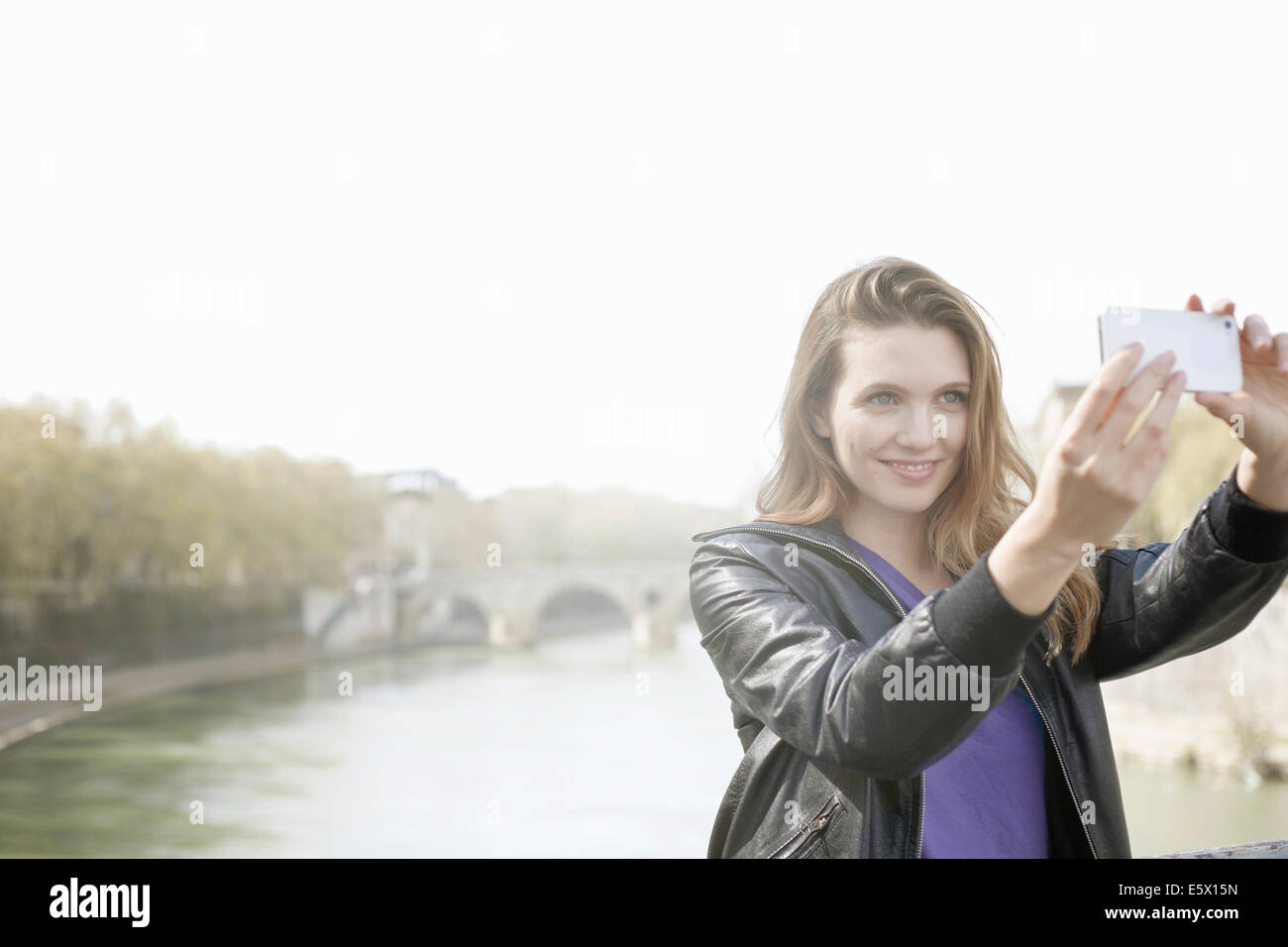 Young woman taking a picture of herself, Isola Tiberina, Rome, Italy - Stock Image
