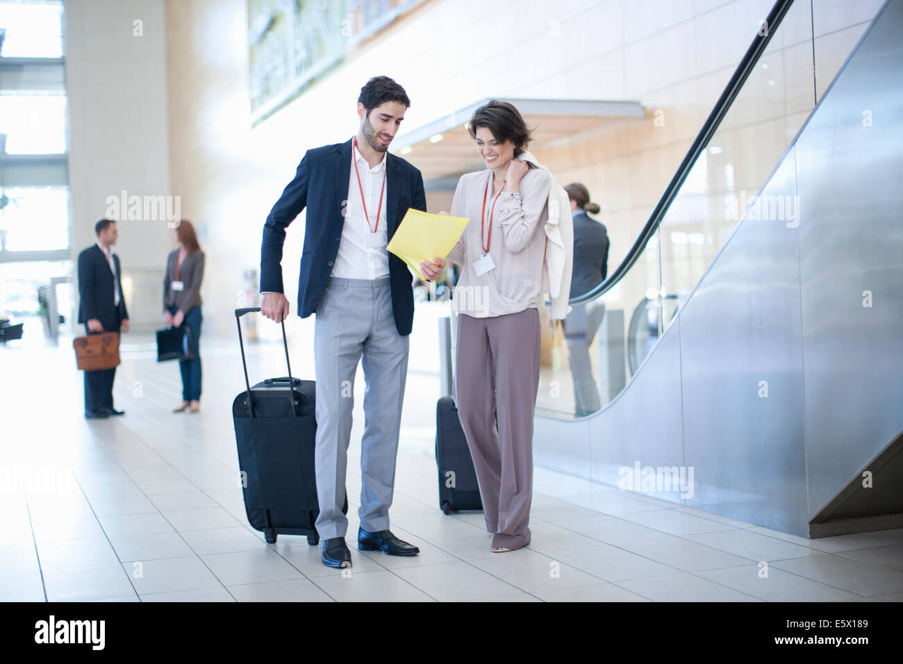 Businessman and businesswoman arriving in conference centre atrium Stock Photo