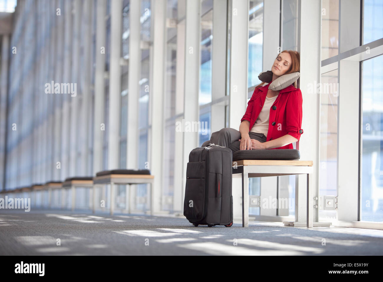 Mid adult businesswoman with wheeled case asleep in conference centre corridor - Stock Image