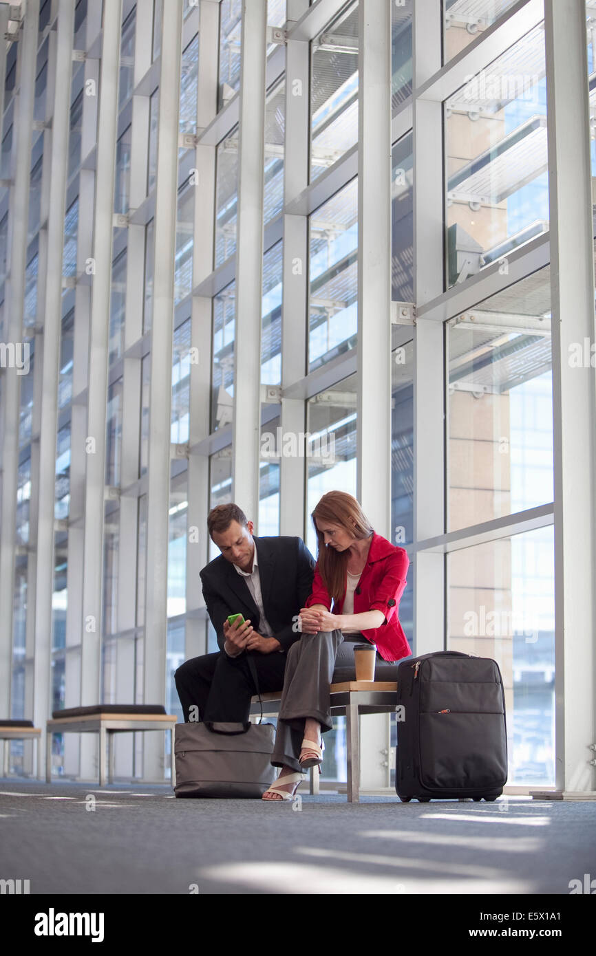 Businesswoman and colleague waiting in conference centre corridor - Stock Image