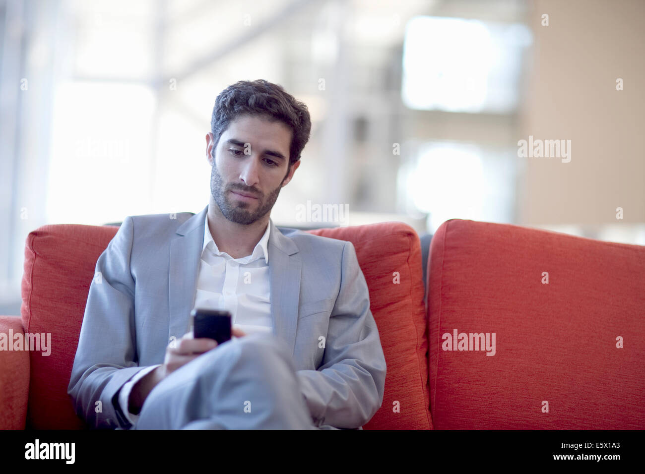 Young businessman smartphone texting on sofa in conference centre - Stock Image