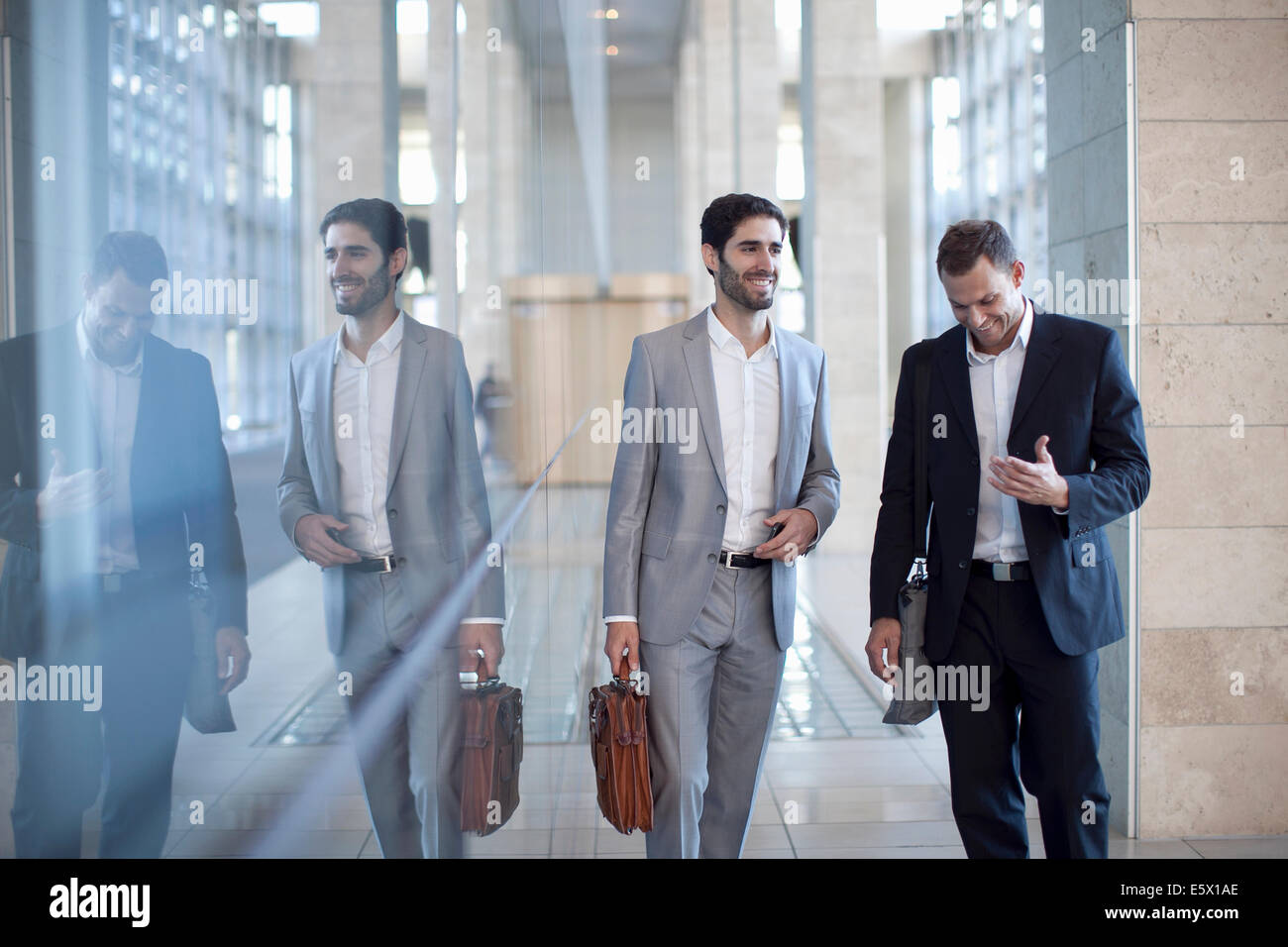 Two young businessmen walking and chatting in conference centre - Stock Image