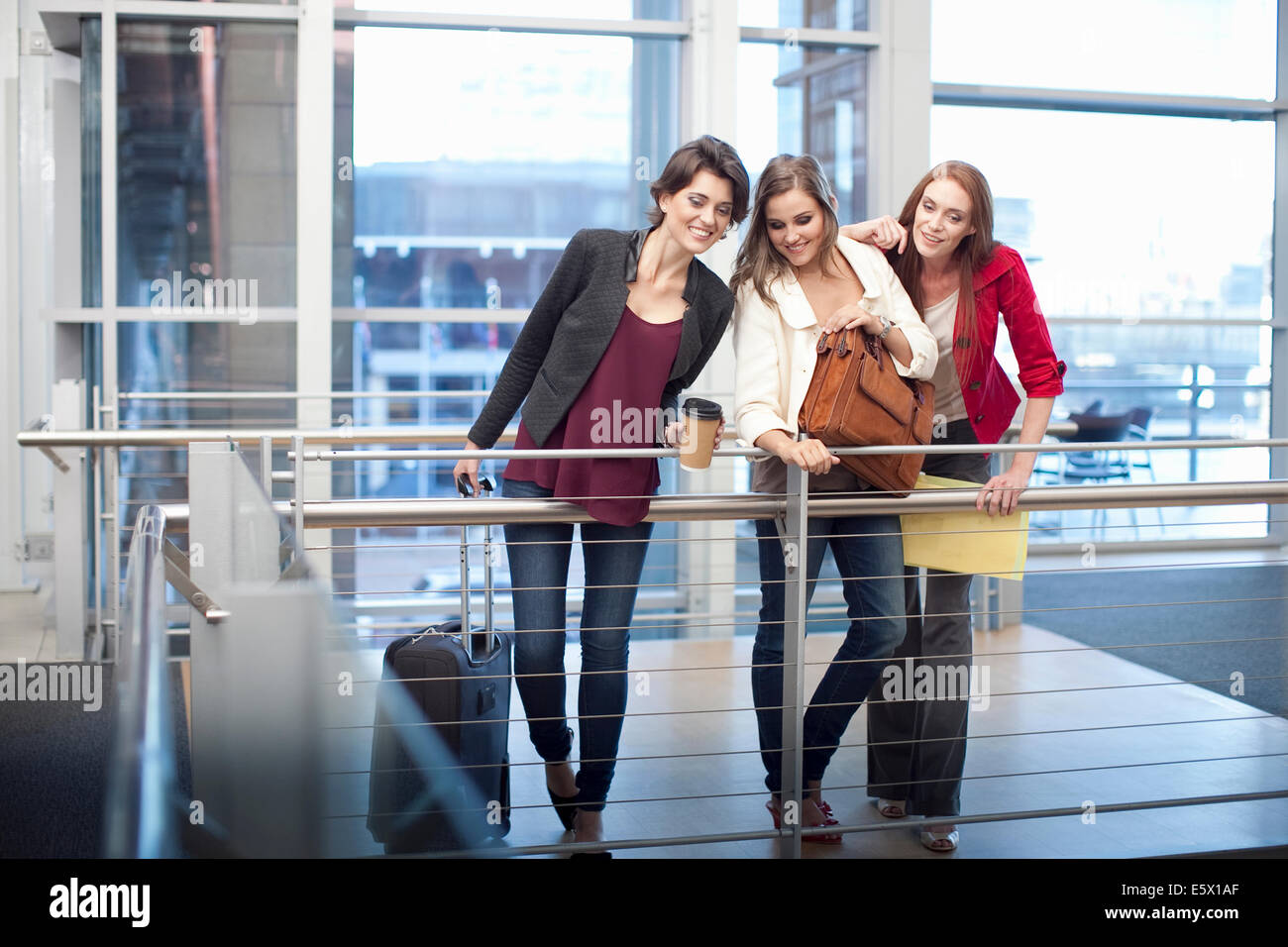 Three businesswomen watching from balcony in conference centre - Stock Image