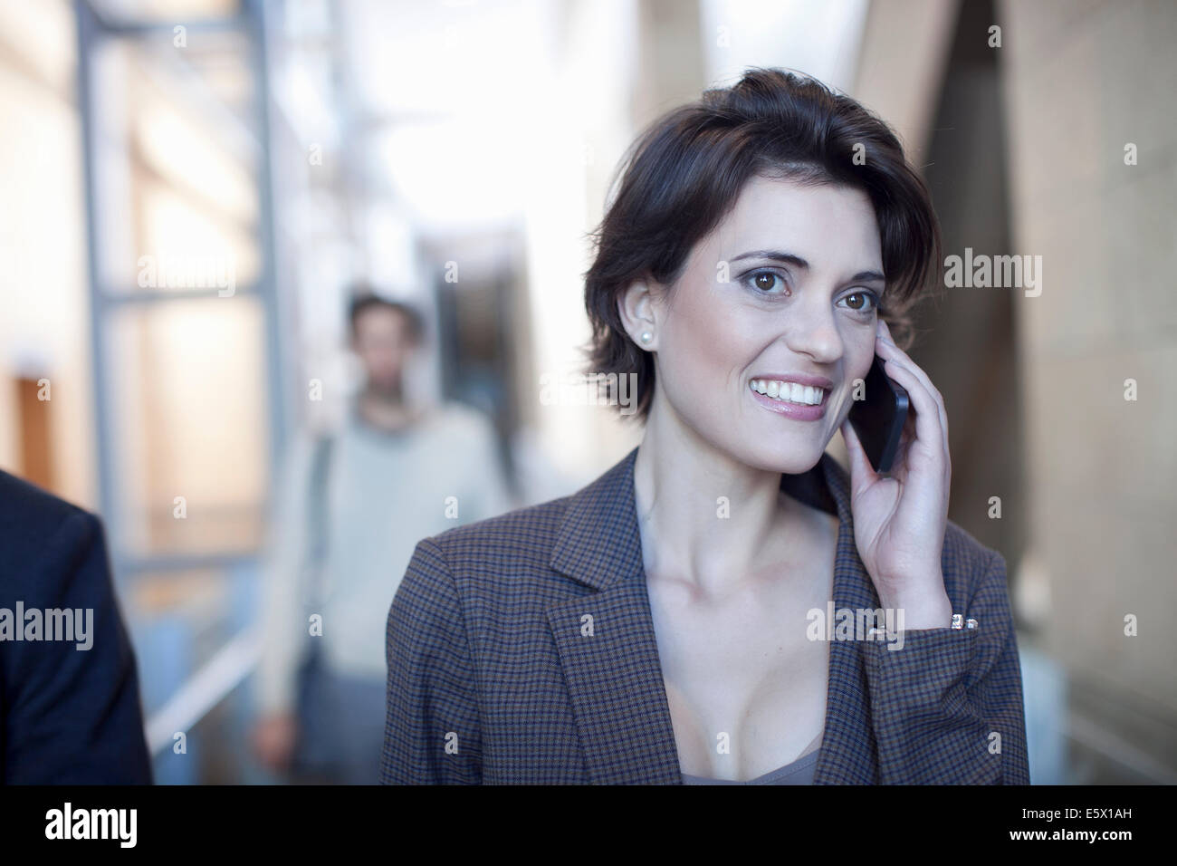 Young businesswoman chatting on smartphone in conference centre - Stock Image