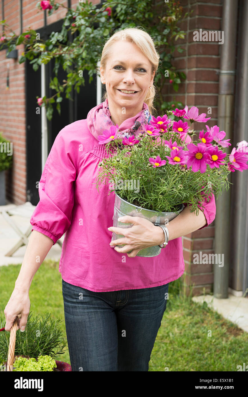 Portrait of mature woman carrying pink flower pot plant in garden - Stock Image
