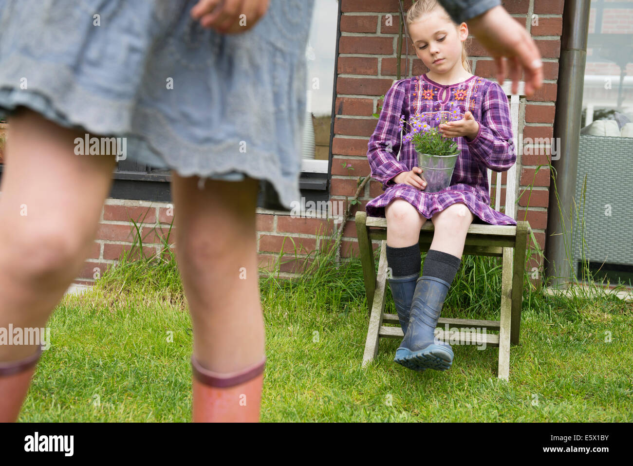 Girl on garden seat gazing at flower pot plant - Stock Image