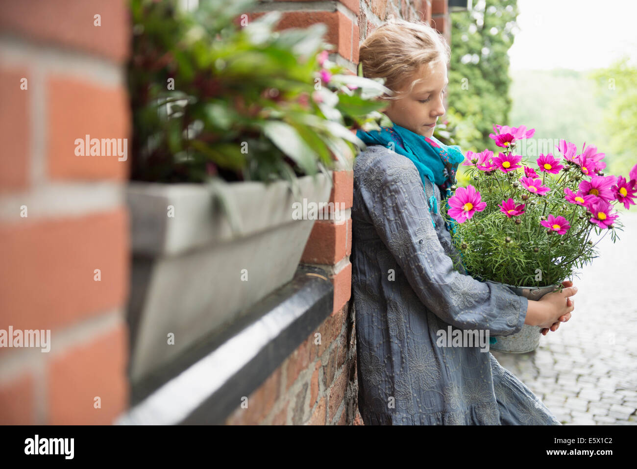 Portrait of girl leaning against wall with flower pot plant in garden - Stock Image