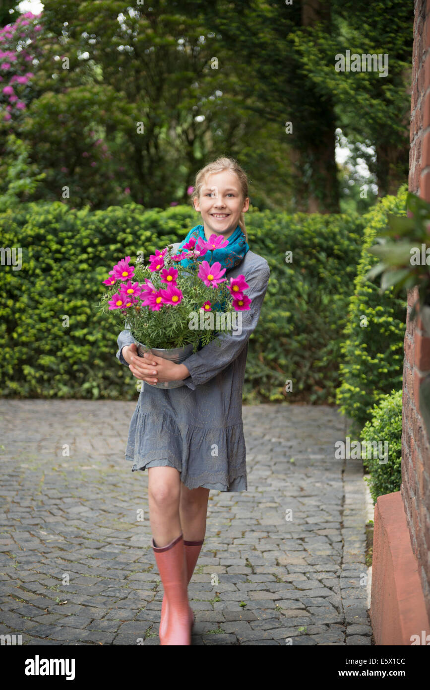 Portrait of girl with flower pot plant in garden - Stock Image