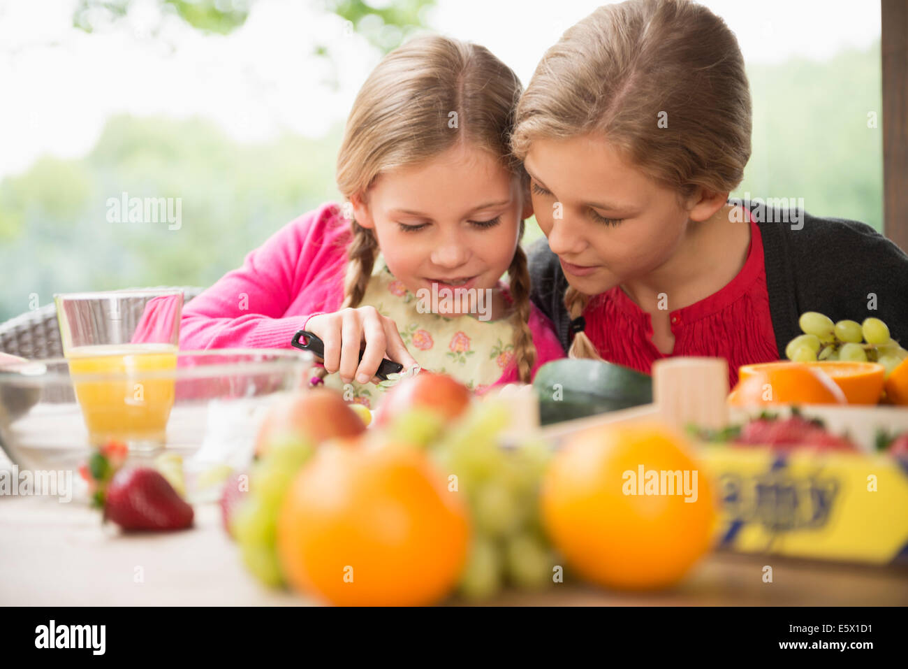 Two sisters at patio table learning to slice fresh fruit - Stock Image
