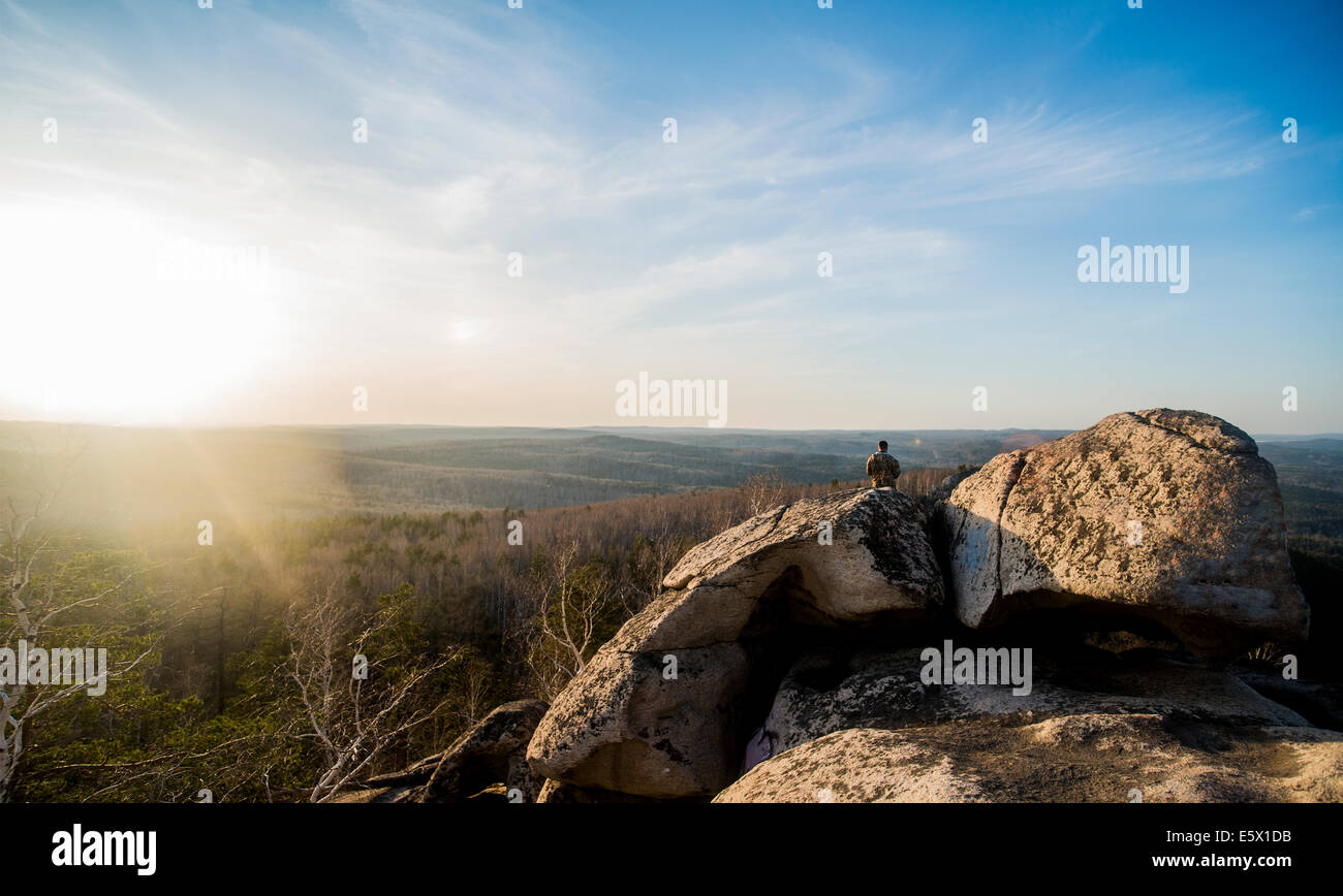 Young male hiker on top of rock formation - Stock Image