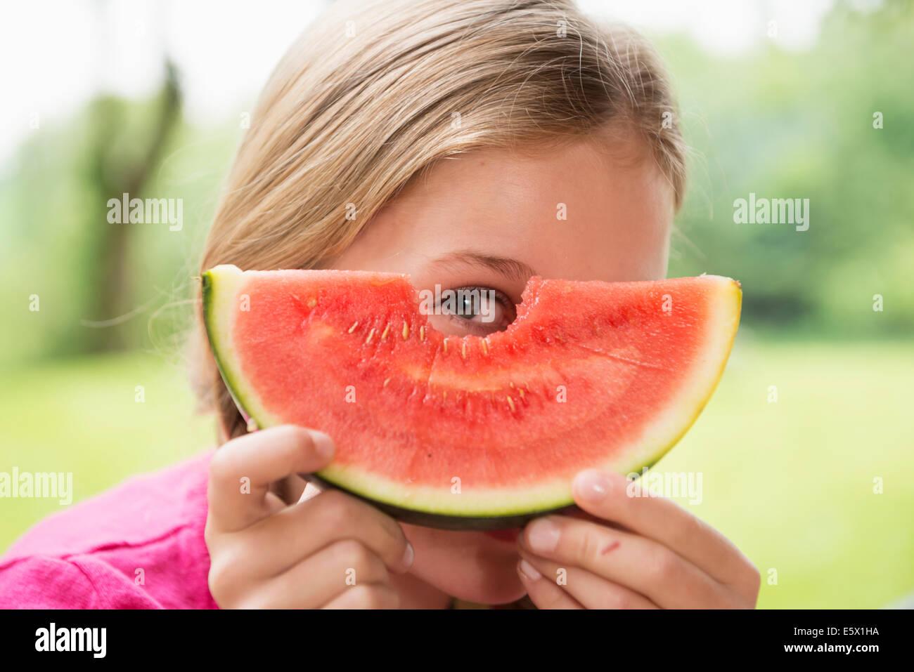 Close up portrait of girl peering through watermelon slice - Stock Image