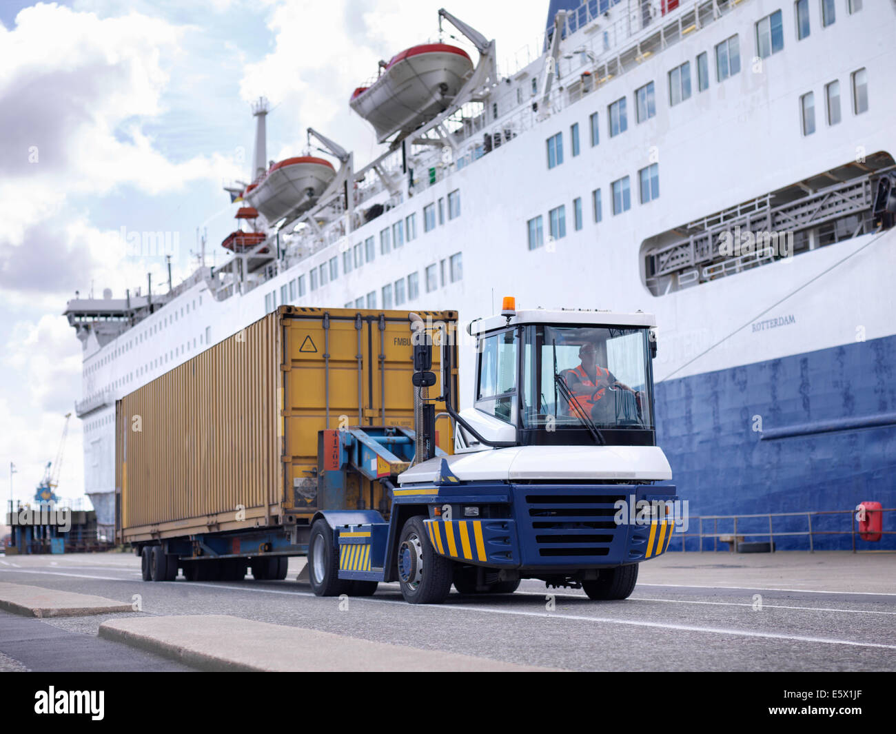 Shipping container and truck by ship in port - Stock Image