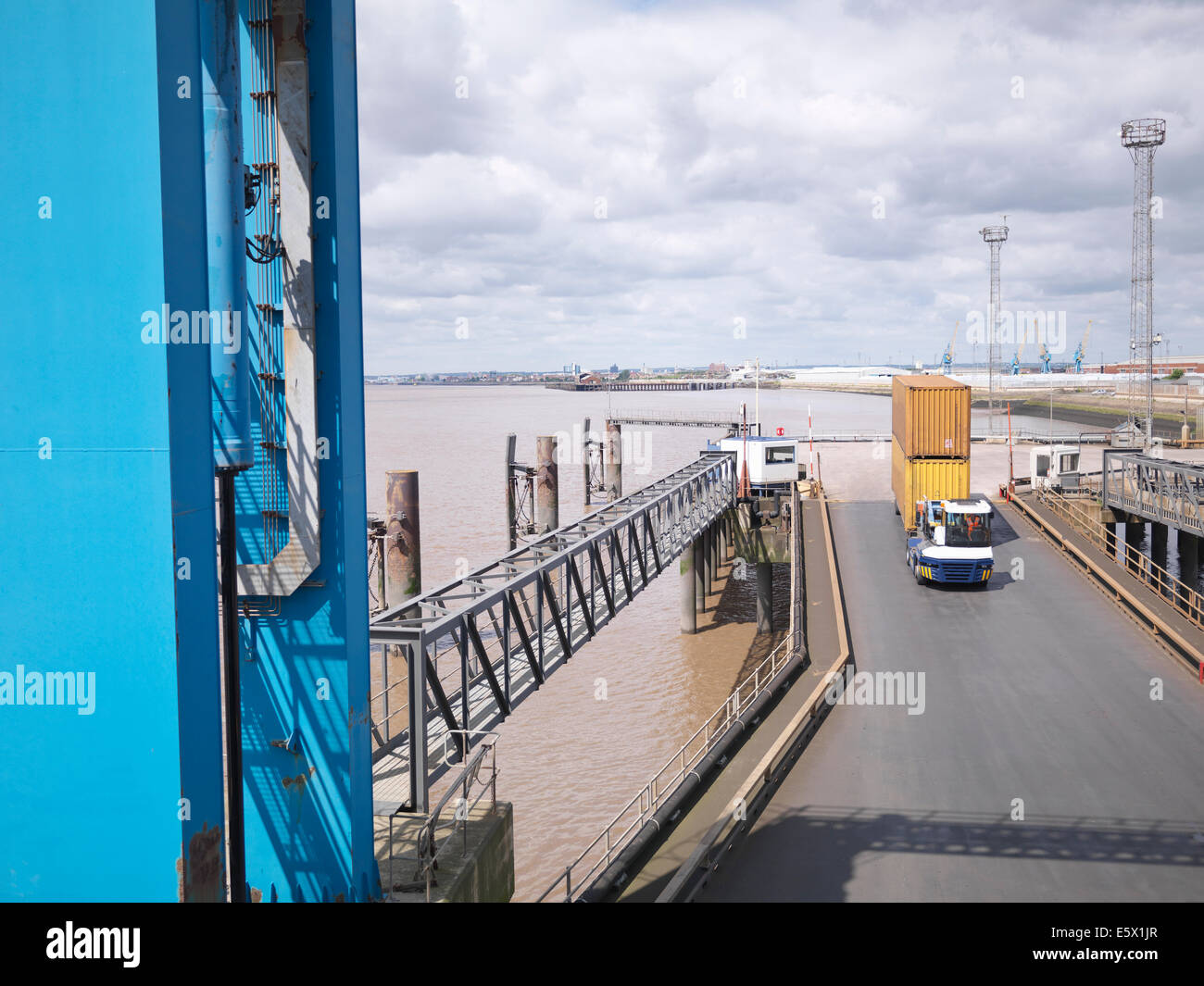 Shipping container and truck on ramp to ship, elevated view - Stock Image