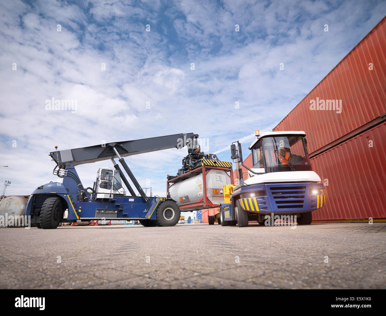 Crane stacking tank containers from truck in port - Stock Image