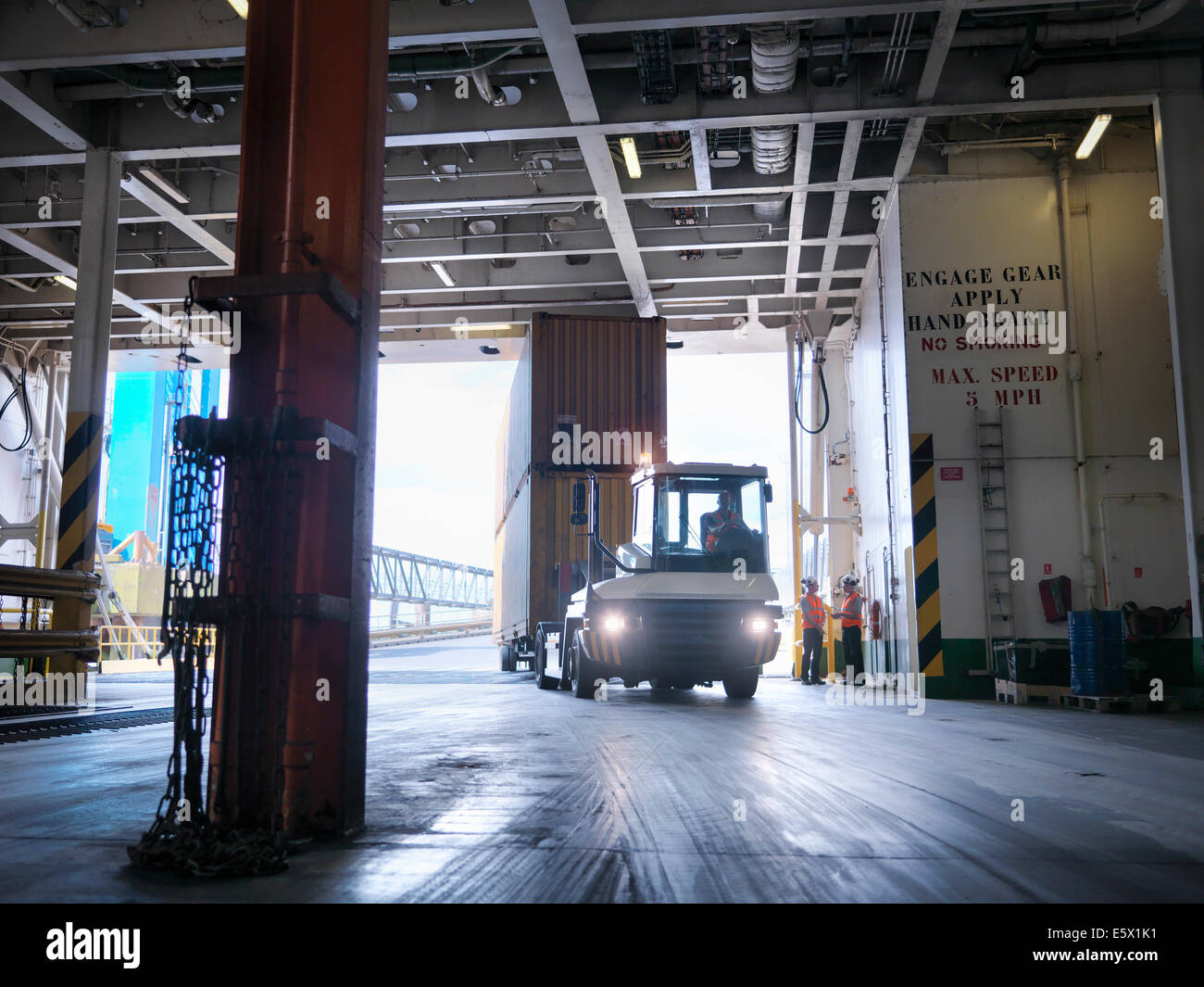 Shipping container being loaded into ship's hold Stock Photo